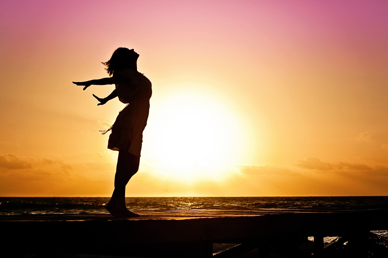 woman standing beside the ocean at sunset doing breathing excercises